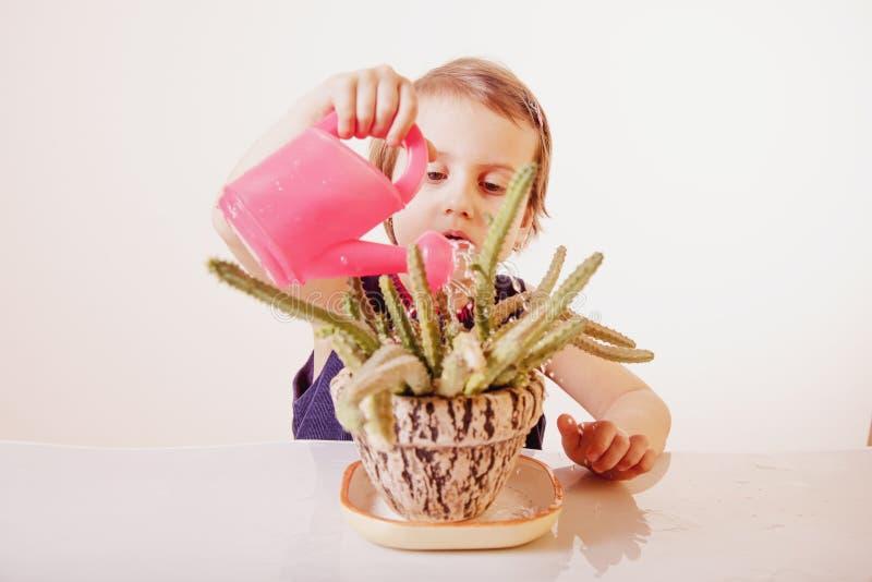 与自然一致的儿童发育 小漂亮的孩子女孩浇灌的花喷壶 家庭,愉快的童年 库存图片