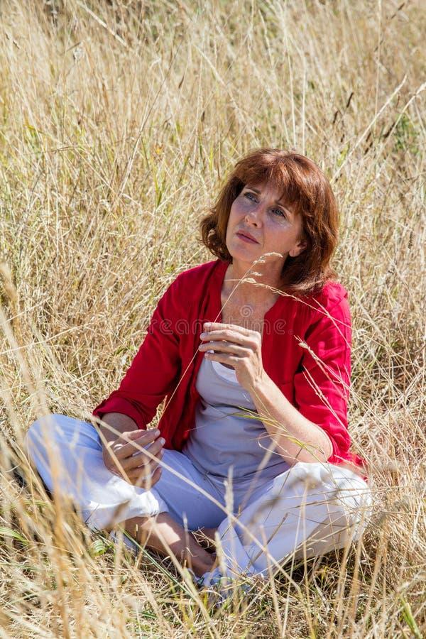 与自然一致的有想象力的年轻资深妇女 免版税库存照片