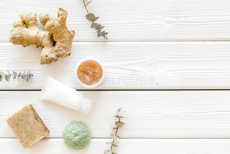 与自然草本和姜成份的化妆用品在白色木背景顶视图copyspace 免版税库存图片