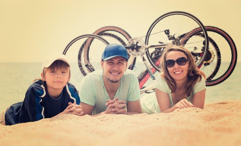与自行车的家庭在海滩 免版税库存照片