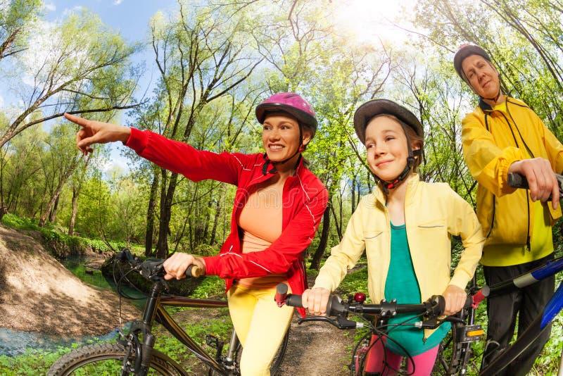 与自行车的愉快的活跃家庭寻找他们的道路的 免版税库存图片