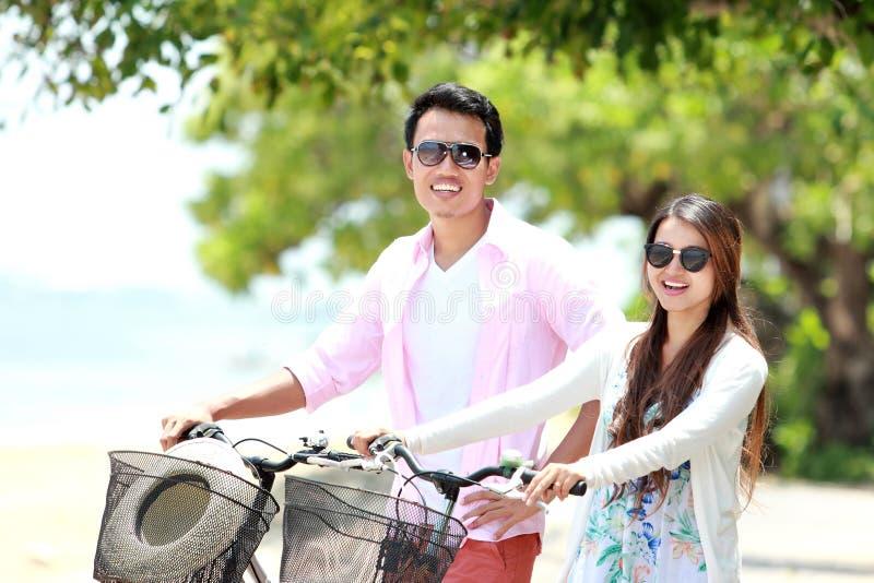 与自行车的年轻夫妇画象在海滩 免版税库存照片