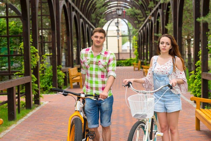 与自行车的年轻有吸引力的对在拱道 免版税库存照片