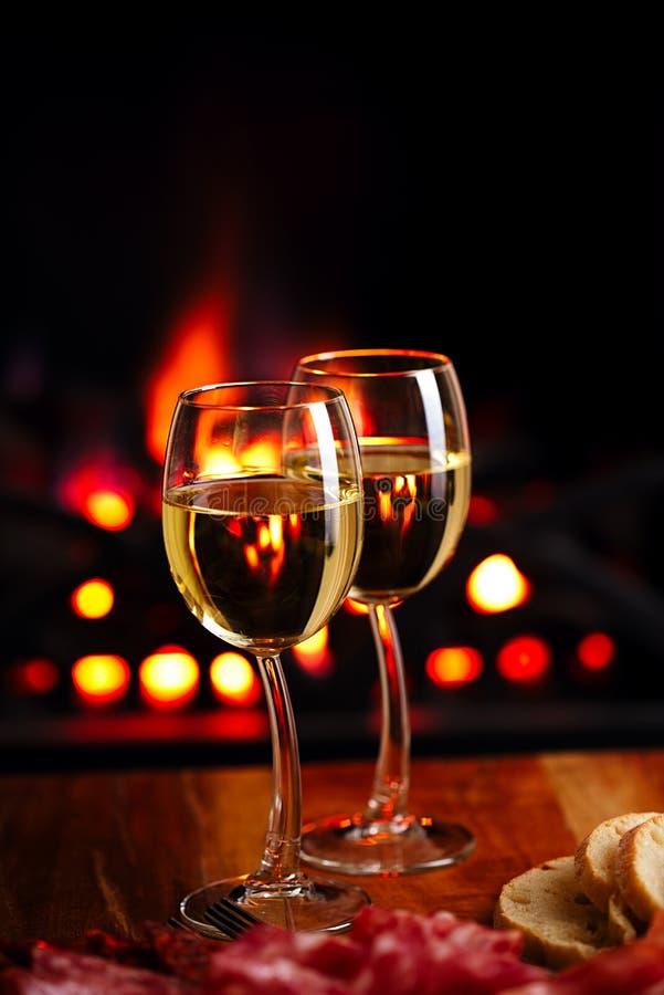与舒适壁炉的两块白葡萄酒玻璃 库存照片