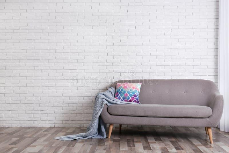 与舒适沙发、枕头和格子花呢披肩的最低纲领派客厅内部在砖墙附近 免版税库存图片