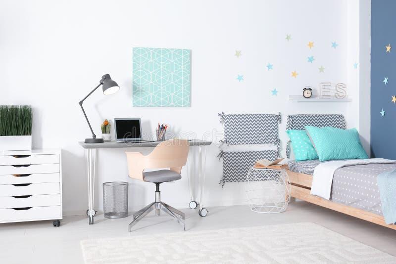 与舒适的床的现代儿童居室内部 图库摄影