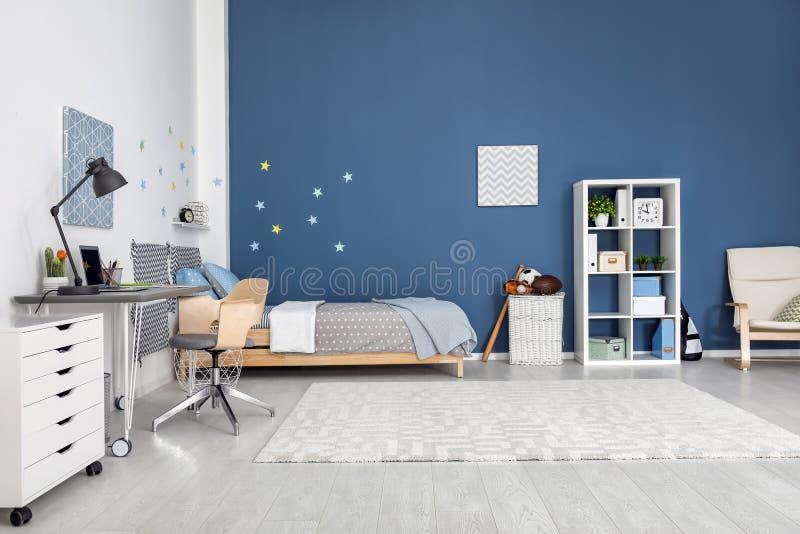 与舒适的床的现代儿童居室内部 免版税库存图片