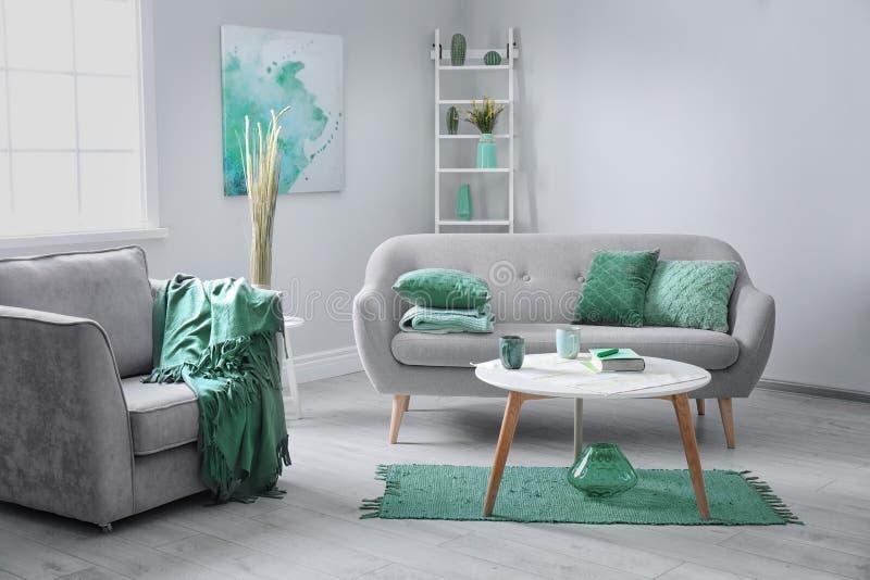 与舒适的扶手椅子和沙发的室内部 薄荷的颜色装饰 免版税库存图片