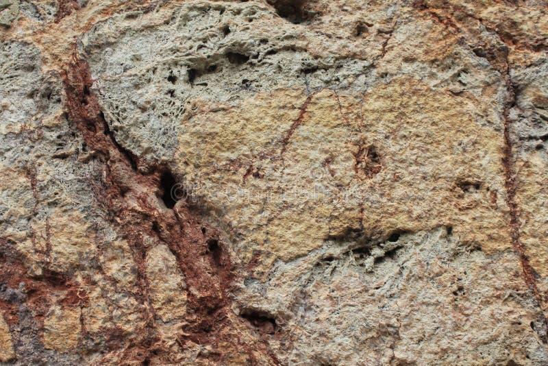 与色土和棕褐色静脉的五颜六色的概略的石背景  库存图片