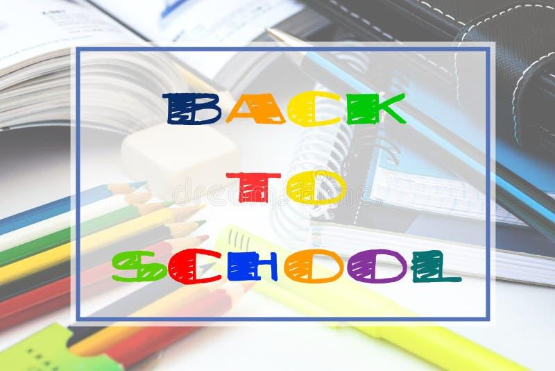 与色的文具的背景书写,笔,笔记本,被打开的课本,白色桌面,与回到学校文字的框架 免版税库存图片