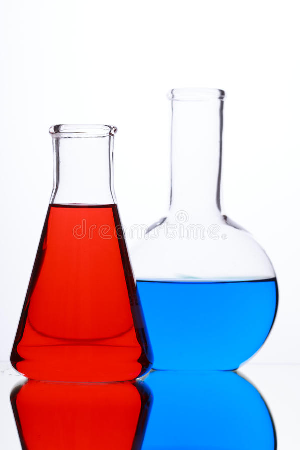与色的液体的玻壳在白色背景 免版税库存照片