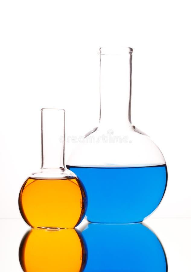 与色的液体的玻壳在白色背景 免版税库存图片