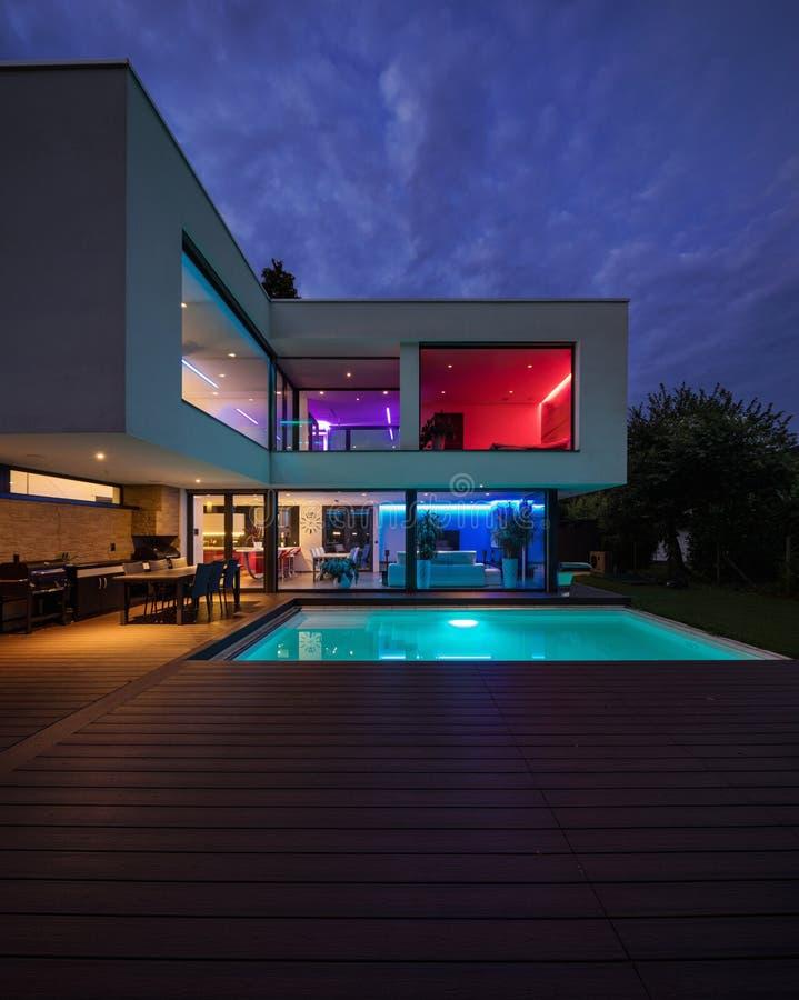 与色的被带领的光的现代别墅在晚上 免版税库存图片