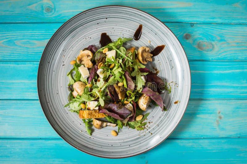 与芝麻菜、乳酪、蘑菇和坚果的新鲜的沙拉在蓝色木背景 免版税库存图片