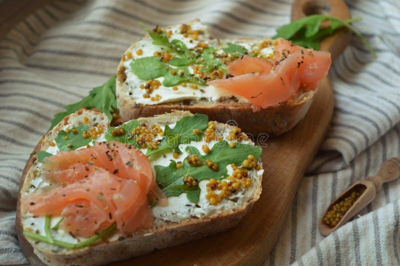 与芝麻菜的两个三文鱼三明治,在木板的芥菜籽 免版税库存图片