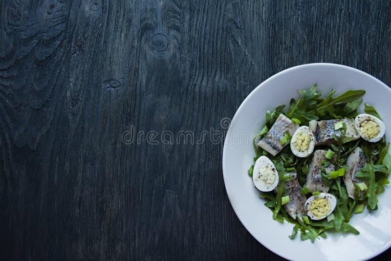 与芝麻菜的用卤汁泡的鲱鱼、葱、煮沸的鹌鹑蛋和柠檬汁和橄榄油 E r ?? 库存图片