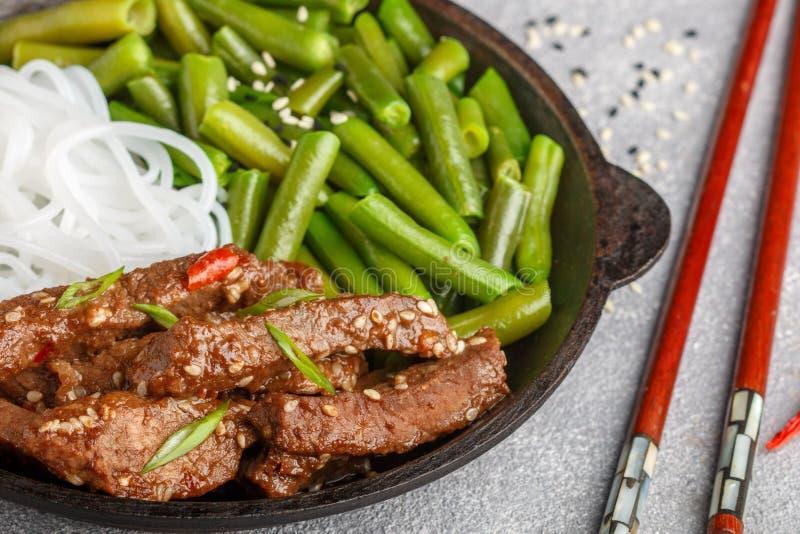 与芝麻籽、青豆和米线的油煎的辣牛肉 库存照片
