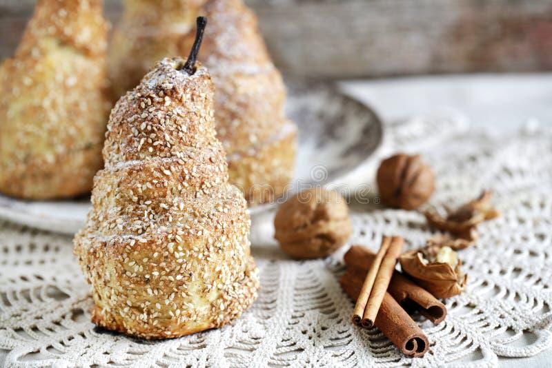 与芝麻籽和桂香,有壳的酥皮点心的被烘烤的梨 库存图片