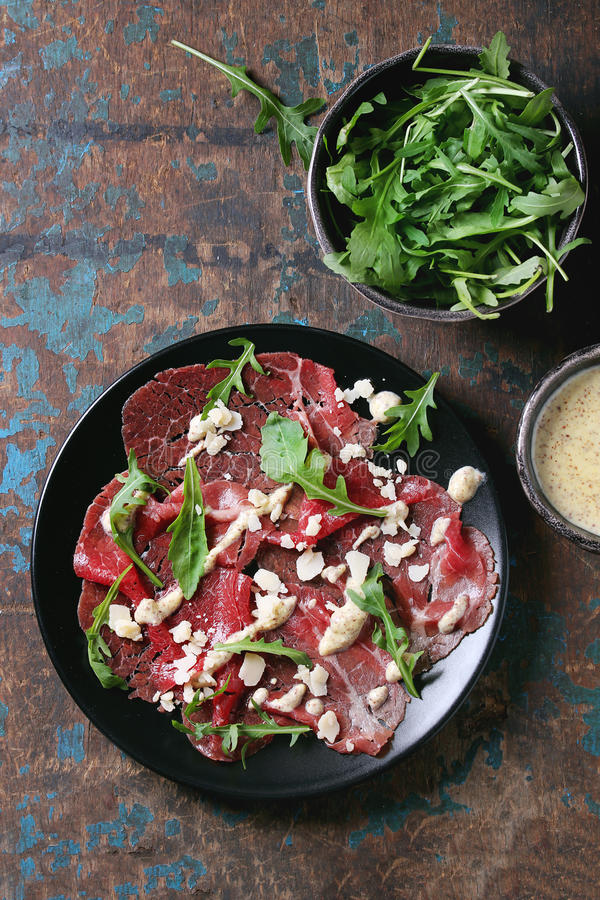 与芝麻菜和调味汁的牛肉carpaccio 库存照片