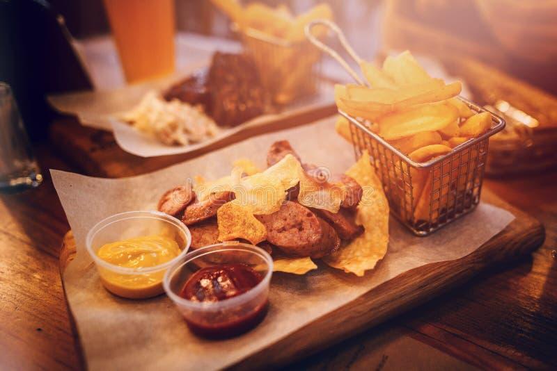 与芯片、炸薯条和调味汁的可口香肠在木b 免版税库存图片