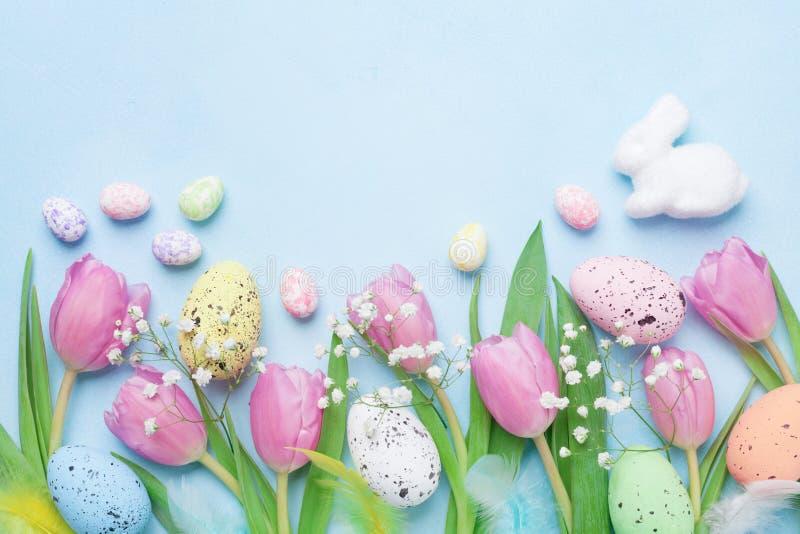 与花、兔宝宝、五颜六色的鸡蛋和羽毛的春天背景在蓝色台式视图 看板卡愉快的复活节 库存图片