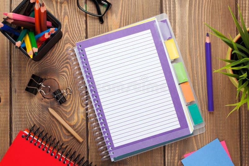 与花、空白的笔记薄和五颜六色的铅笔的办公室桌 免版税库存图片