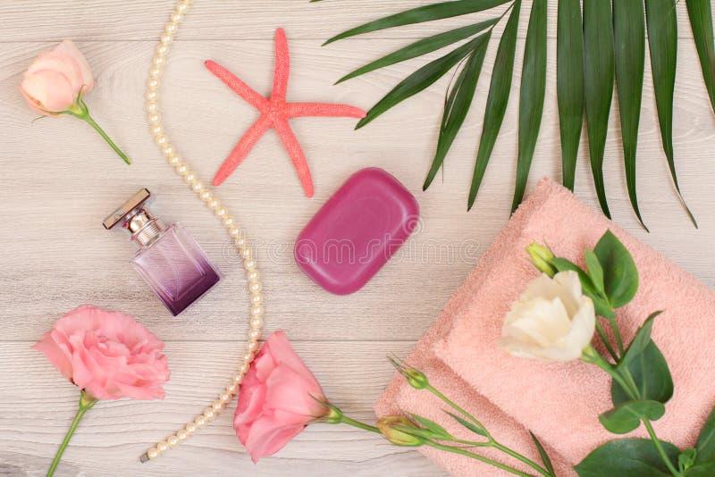 与花、肥皂和香水的软的特里毛巾在木板 库存照片