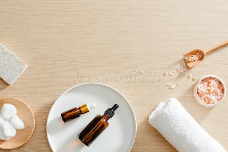 与花、自然油、腌制槽用食盐和毛巾,温泉skincare产品,浮岩的温泉静物画顶视图 免版税库存图片