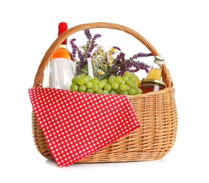 与花、酒和食物的野餐篮子 图库摄影