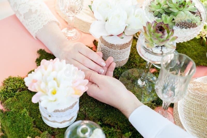 与花、青苔和多汁植物的浪漫桌设置 新娘和新郎的手被加入 o 免版税图库摄影
