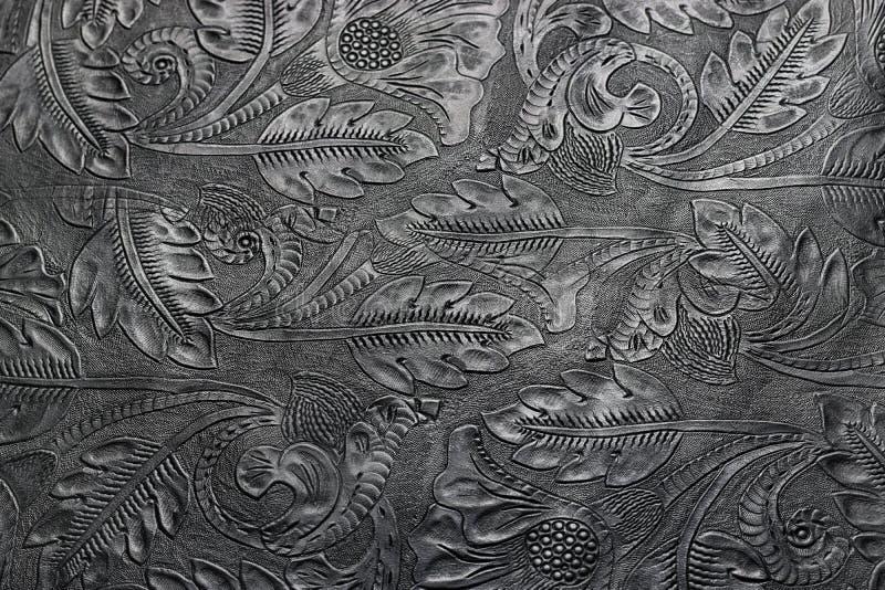 与花卉主题的压印的发光的黑皮革 库存图片