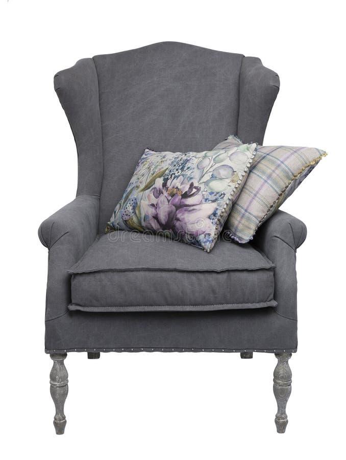 与花卉和方格的坐垫的传统灰色胳膊椅子 免版税库存照片