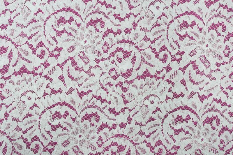 与花卉样式的白色鞋带织品在红色 免版税库存图片
