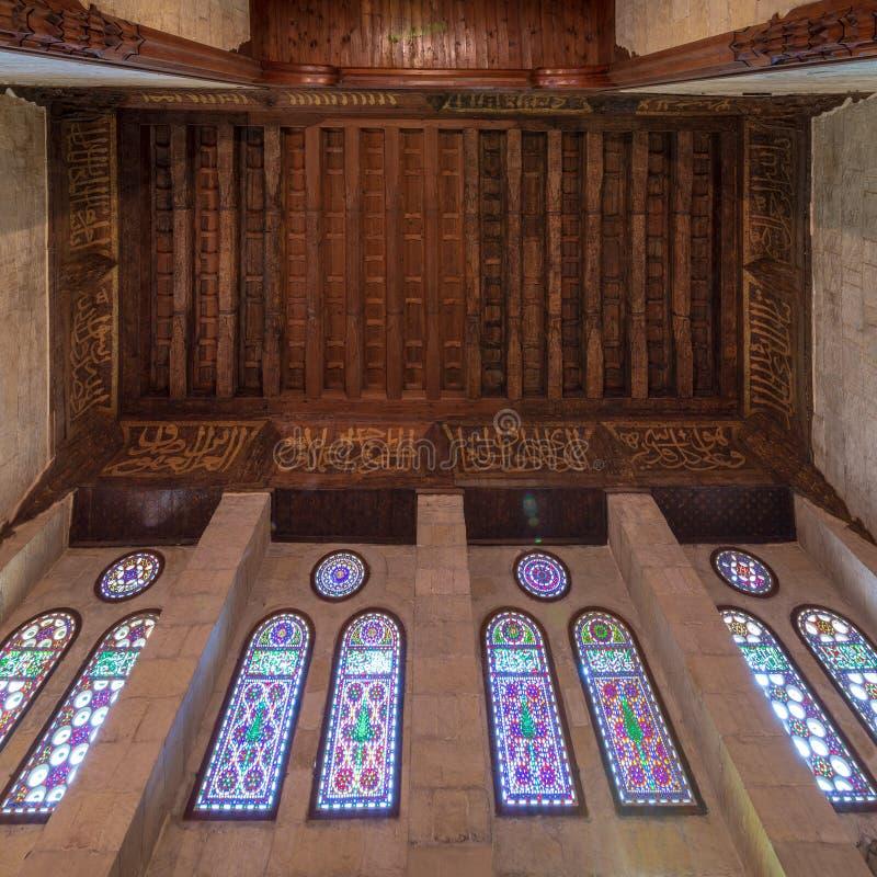 与花卉样式装饰和五颜六色的污迹玻璃窗,苏丹Al Ghuri陵墓,开罗,埃及的木华丽天花板 免版税库存照片
