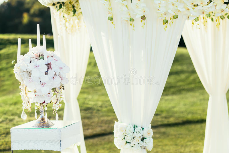 与花和Ñ  andle装饰的婚礼曲拱在晴天在仪式放 免版税库存图片