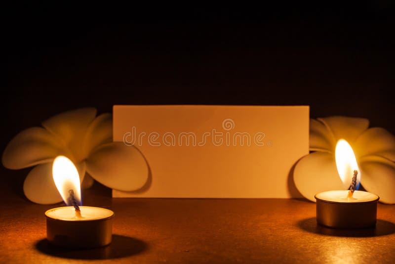 与花和便条纸的静物画蜡烛,抽象背景为祈祷或凝思说明 库存图片