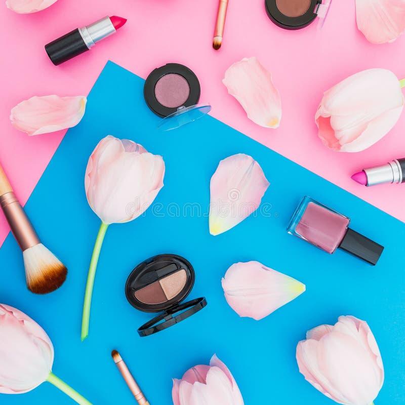 与花和女性化妆用品的蓝色和桃红色淡色背景 平的位置 顶视图 库存照片