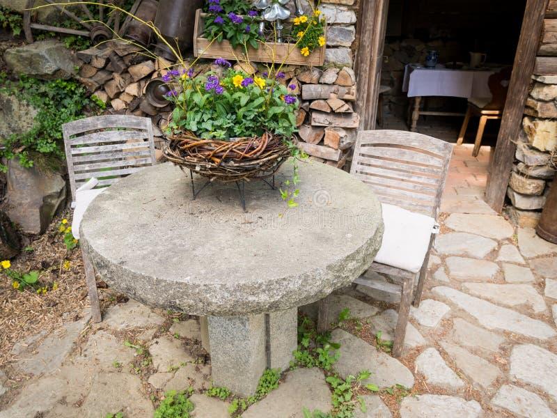 与花和椅子的石桌在庭院里 库存照片