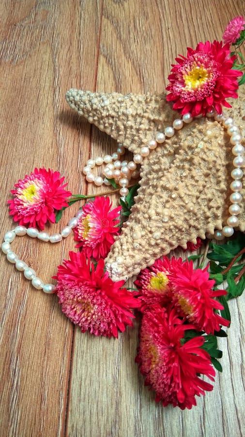 与花和珍珠的海星 免版税库存照片