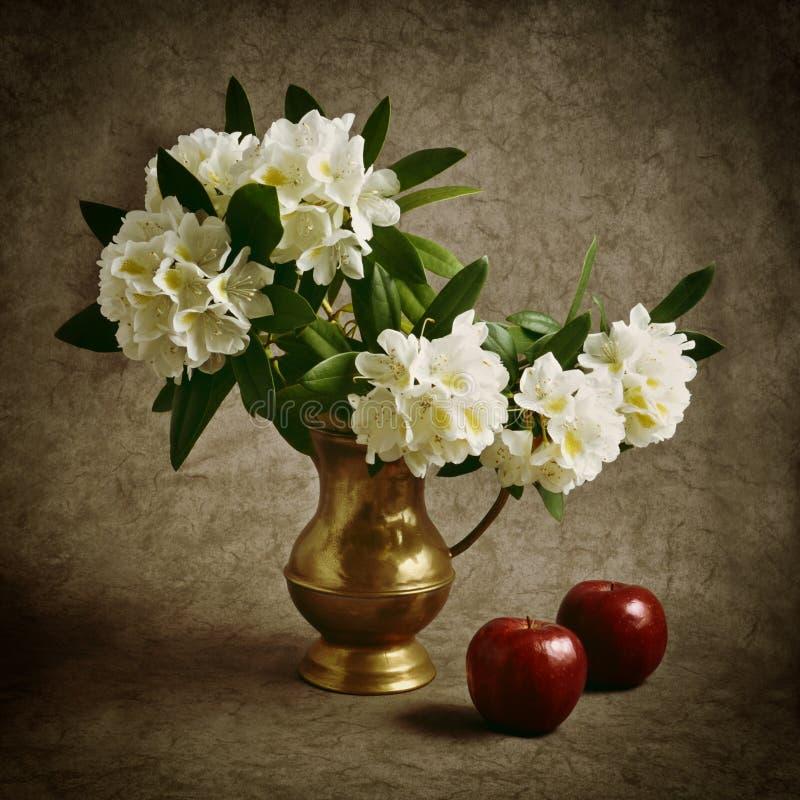与花和红色苹果的静物画 免版税库存照片
