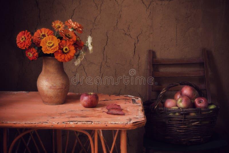 与花和苹果的静物画在背景老墙壁上 库存图片