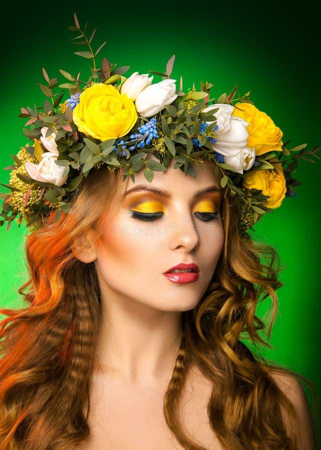 与花圈的时装模特儿在绿色背景 库存图片