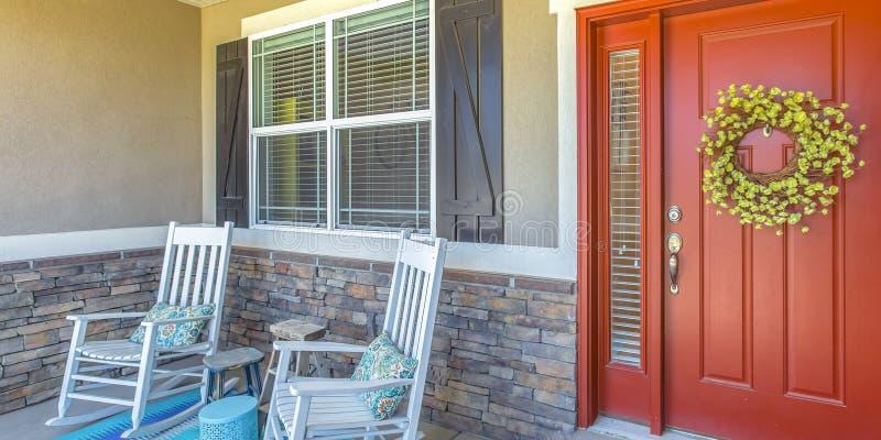 与花圈的红色在门廊的前门和椅子 图库摄影