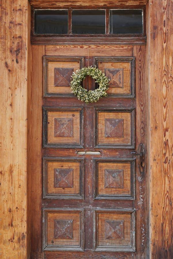 与花圈的老破旧的木前门 库存照片