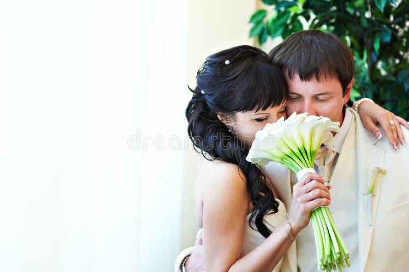 与花束的愉快的新娘和新郎 免版税图库摄影