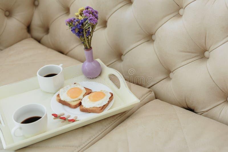 与花束的浪漫早餐在长沙发 免版税库存图片
