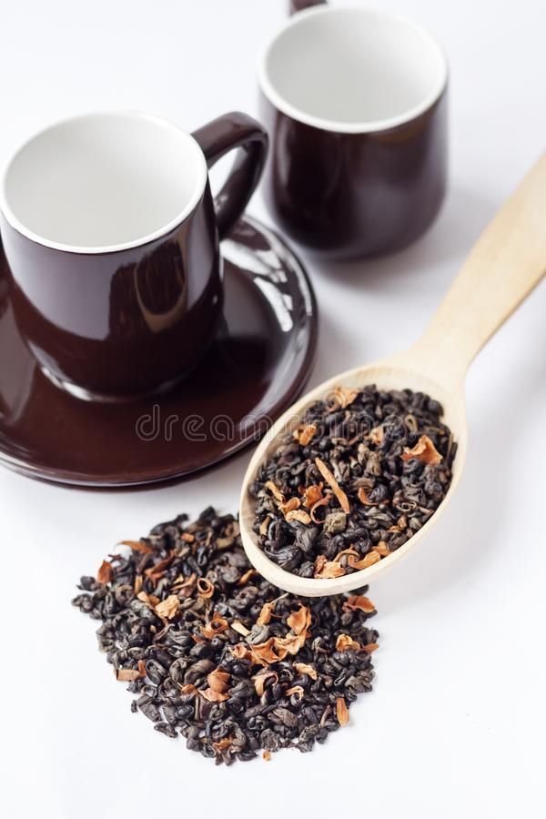 与花瓣的干绿色茶叶在木匙子 免版税库存图片