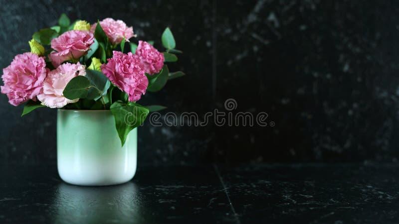 与花瓶的黑大理石柜台与拷贝空间的桃红色lisianthus花 免版税库存图片