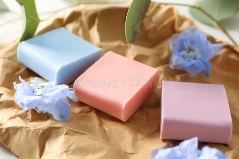 与花的不同的肥皂酒吧在压皱纸 库存照片