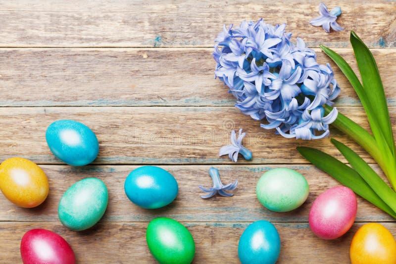 与花的五颜六色的复活节彩蛋背景在木土气台式视图 春天贺卡为假日 免版税库存照片